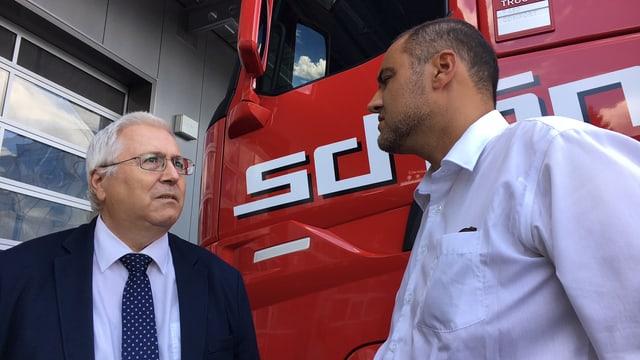 Zwei Männer stehen vor der Führerkabine eines roten Lastwagens und diskutieren.