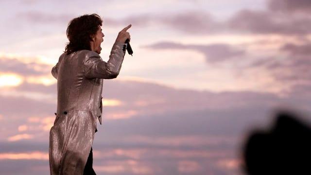 Mick Jagger in silberglänzendem Kittel vor einem dramatischen Abendhimmel, die Hand mit dem Mikrofon zeigt auf das Publikum.