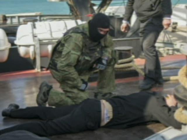 Ein Maskierter kniet neben einem Mann, der sich die Hände über den Kopf hält.