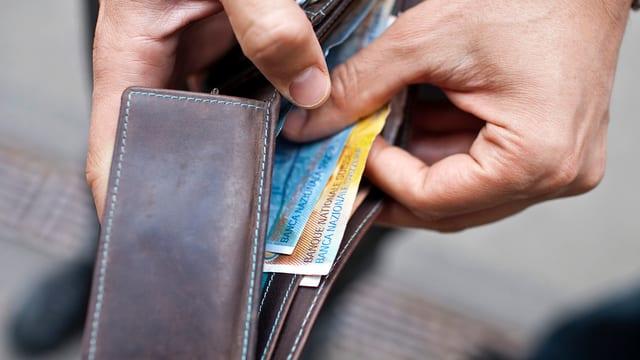 Ein Mann zieht Geld aus seiner Brieftasche.