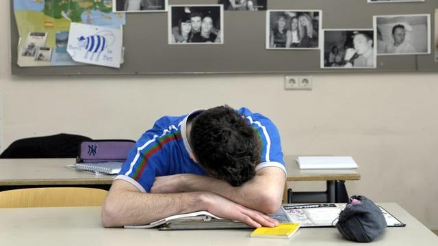 Ein Schüler sitzt schlafend vornüber gebäugt am Pult.
