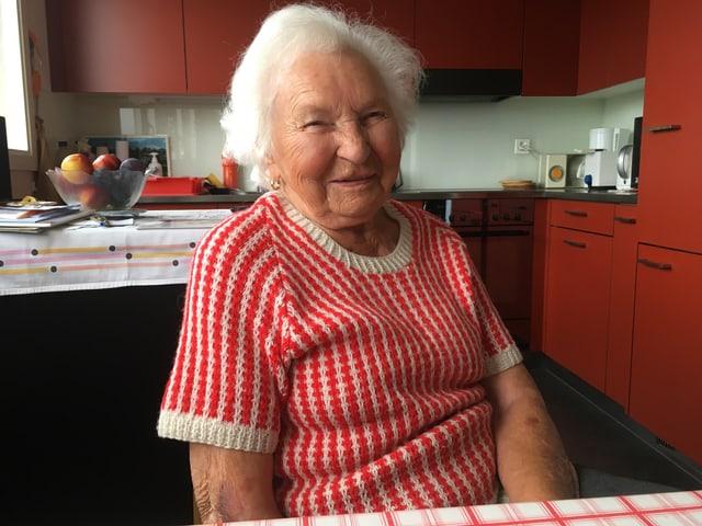 Seniorin sitzt in moderner, rot gestalteter Küche.