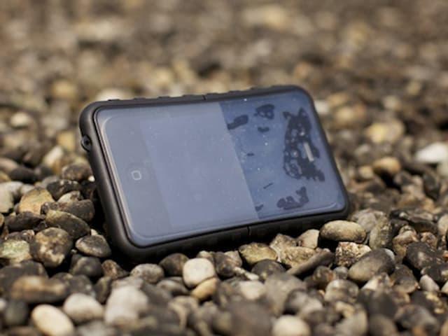 Ein Smartphone in Silikonhülle liegt auf einem Kiesboden.