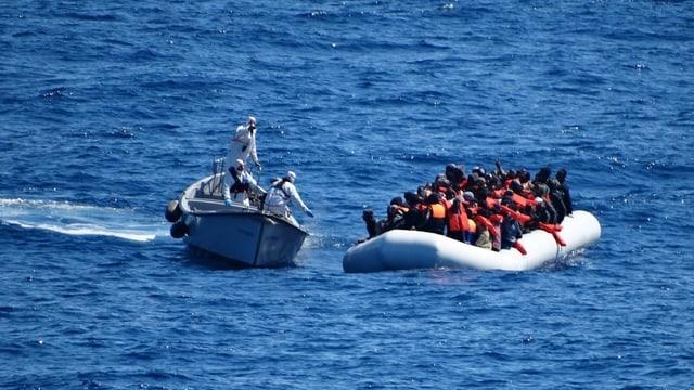 Ein Schiff der italienischen Marine nähert sich einem Schlauchboot.