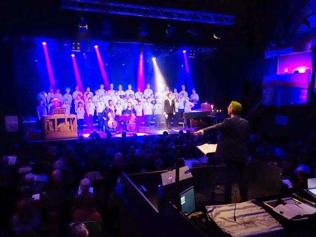Reize dirigiert von der Mitte des Raumes aus den Chor, welcher blau beleuchtet wird.