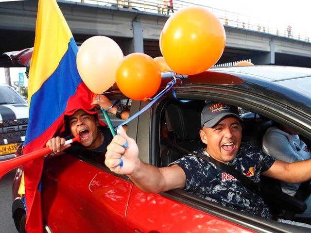 Männer in einem Auto halten die kolumbianische Flagge.