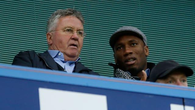 Interimstrainer Guus Hiddink und Didier Drogba sitzen gemeinsam auf der Tribüne.
