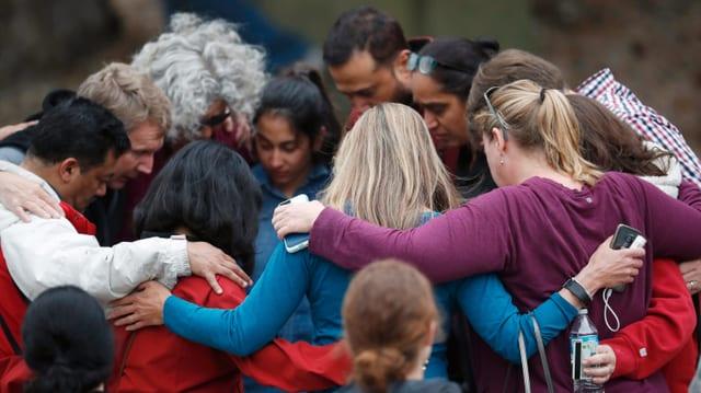 Trauernde Menschen umarmen sich