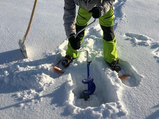 Ein Mann bohrt ein Loch ins Eis auf einem Bergsee.