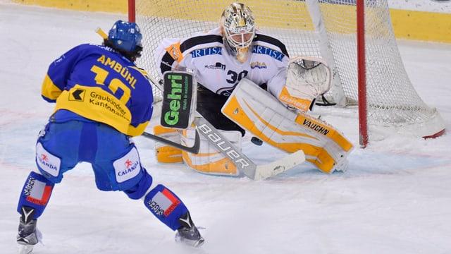 In giugader da hockey cun in tricot blau davant la porta dal goli cun in tricot alv. L'attatgader sajetta il disc ed il goli emprova da franar quel.