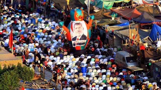 Betende Muslime in Kairo. In der Bildmitte ein Transparant mit Mursi-Konterfei.