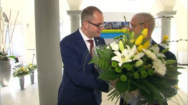 Ein Mann übergibt einem anderen Blumen.