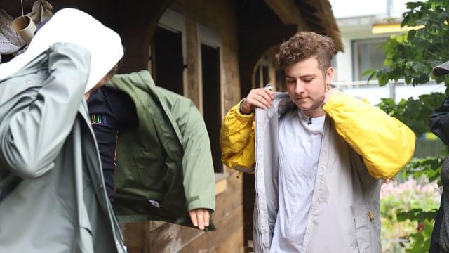 Luca zieht seine Regenjacke an
