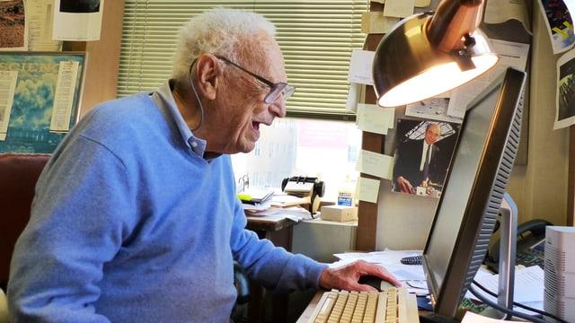 David Perlman sitzt an seinem Arbeitstisch und guckt in den Computer.
