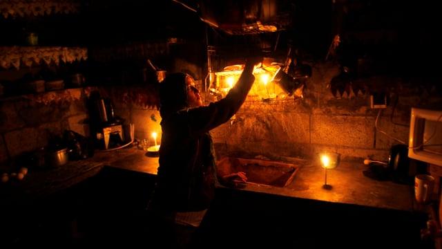 Eine Frau arbeitet in einer Küche, die nur von verschiedenen Kerzen beleuchtet ist.