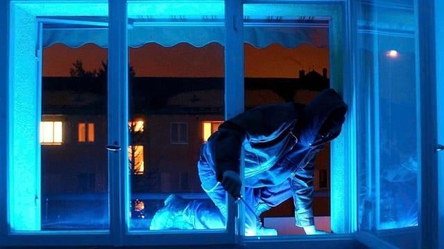 Mann steigt in Dunkelheit über Fenster ein