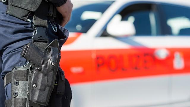 polizist da la Polizia chantunala davant in auto da polizia