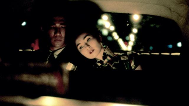Ein Mann und eine Frau sitzen auf der Rückbank eines Autos, sie legt den Kopf auf seine Schulter