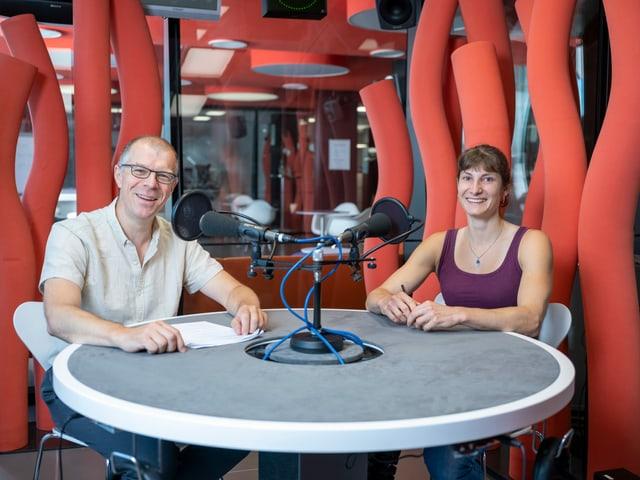 Markus Gasser und Nadia Zollinger sitzen vor zwei Mikrophonen.