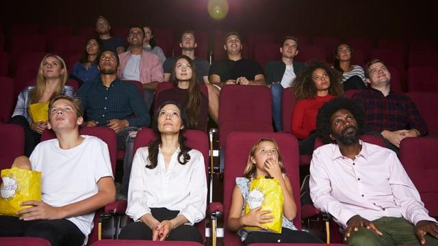 Mehrere Reihen von Männern, Frauen und Kindern schauen Kino und essen Popcorn
