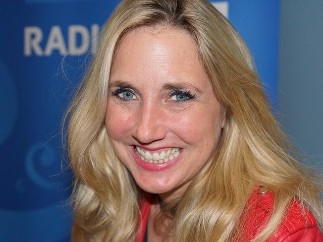 Eine lachende Frau mit langen blonden Haaren.