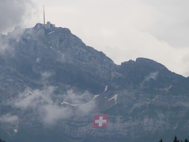 Säntis mit Wolken und Schweizer Flagge im Felsen