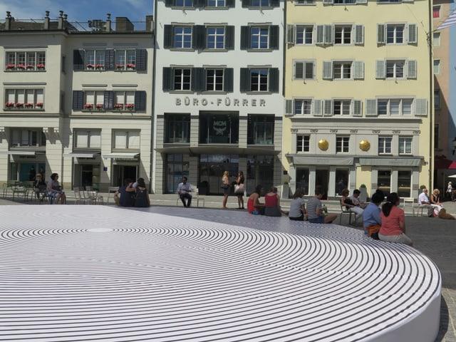 Eine grosse runde Matte mit schwarzen und weissen Streifen auf dem Münsterplatz. Ein paar Passanten sitzen darauf.