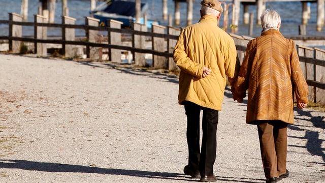 Ein älteres Ehepaar spaziert an einem See.