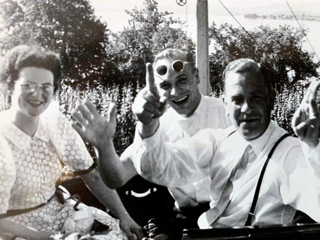 Drei Personen sitzen in einer Kutsche.