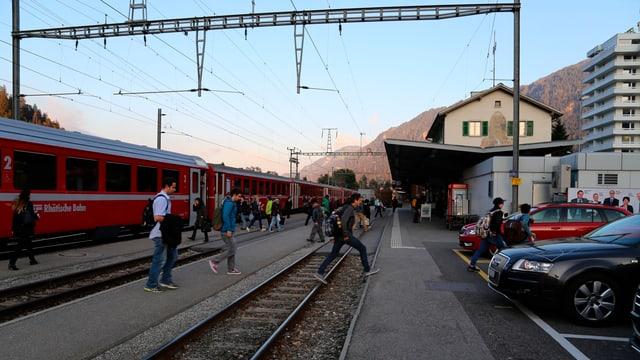 Ina staziun cun in tren e passagiers che sortan dal tren.