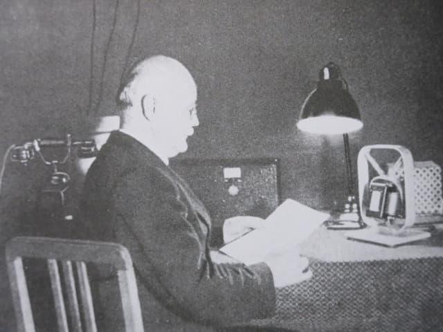 Schwarzweiss-Aufnahme eines Mannes, der an einem Tisch sitzt und liest.