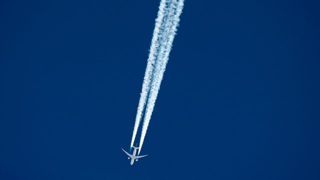 Flugzeug und Kondensstreifen.