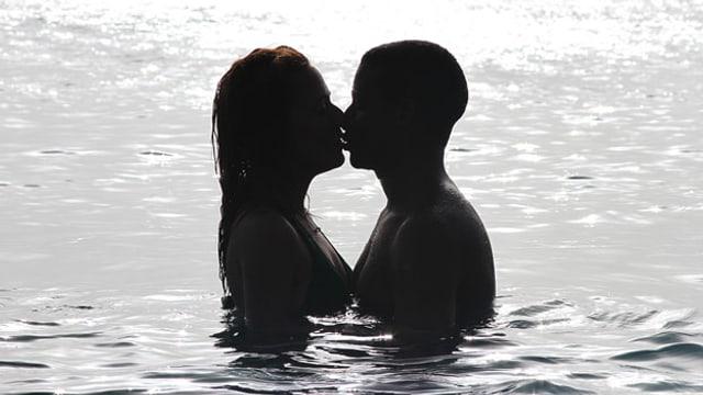 Ein Paar im Meer stehend, sich küssend im Sonnenuntergang