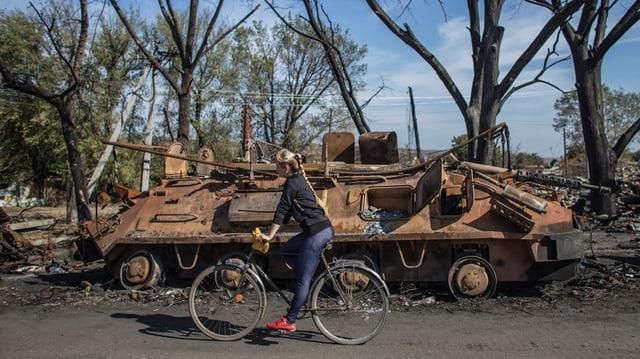 Frau fährt auf Fahrrad vor zerstörtem Panzer vorbei.