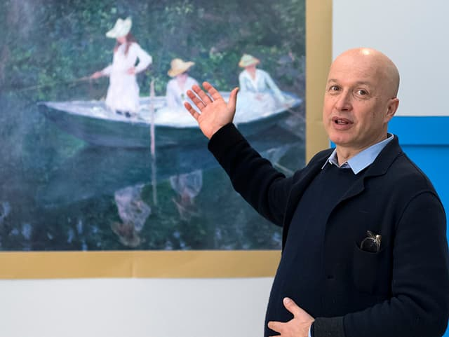 Sam Keller steht vor einem Monet Bild und zeigt auf dieses. Das Bild ist aber nur eine Reproduktion.