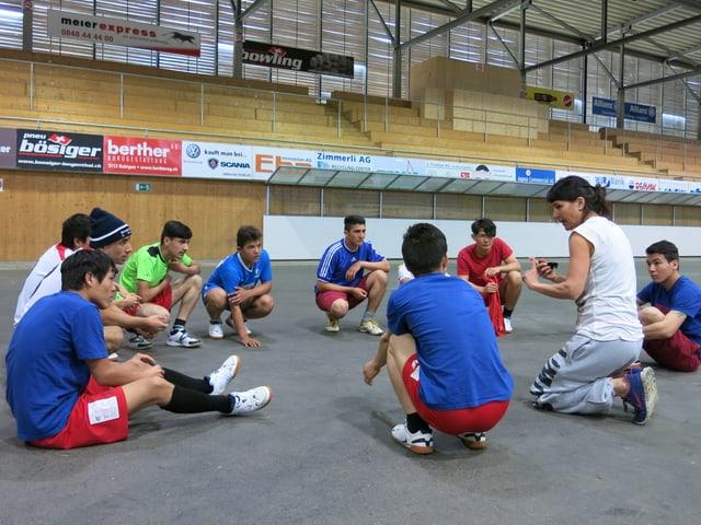 Sportlehrerin sitzt im Kreis mit jugendlichen Asylsuchenden.