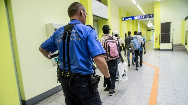 Ein Grenzwächter begleitet Migranten zur Personenkontrolle bei der Grenzkontrolle am Zoll des Bahnhofs Chiasso.