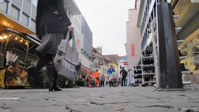 Eine Frau läuft mit einer Einkaufstasche durch die Einkaufspassage in Aarau.