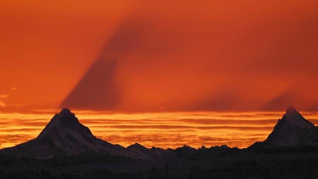 Oranger Himmel, Berge mit Schattenwurf.