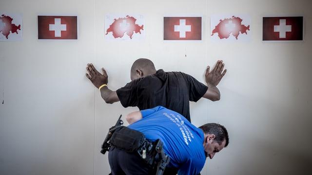 Ein Grenzwächter untersucht einen Flüchtling.