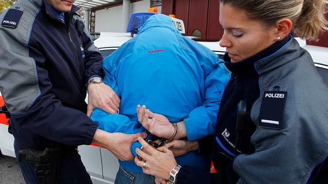 Polizisten verhaften einen Mann (gestellte Szene)