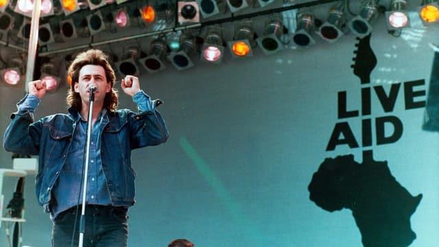 Ein Mann mit mittellangen Haaren und Jeansjacke auf der Bühne mit dem Logo Live Aid.