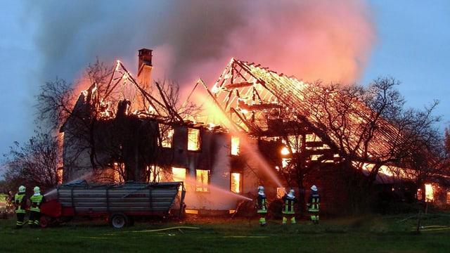 Feuerwehrleute versuchen einen brennenden Bauernhof zu löschen.