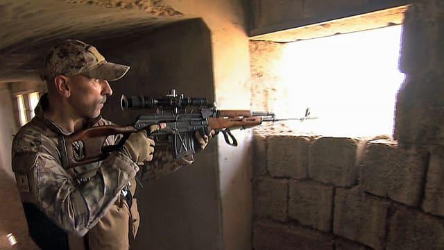 Ein Mann im Kampfanzug mit Sturmgewehr legt bei einem Fenster an.