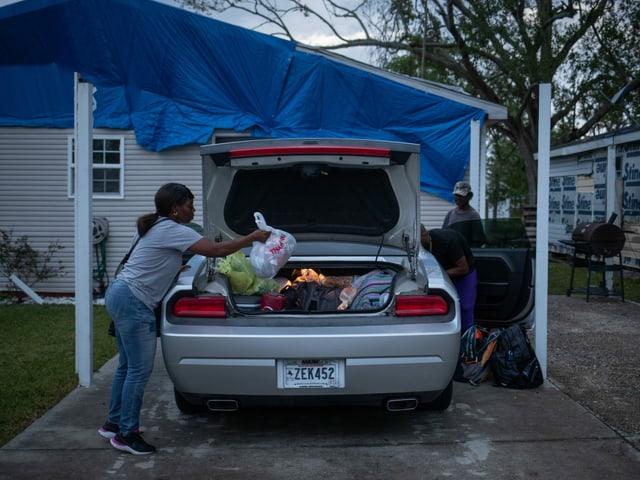 Frau packt Gepäck in Kofferraum. Im Hintergrund sind zwei männliche Personen.