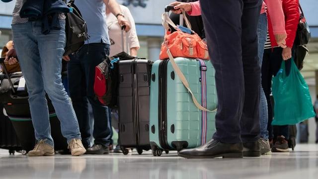 Reisende mit Koffern am Flughafen.