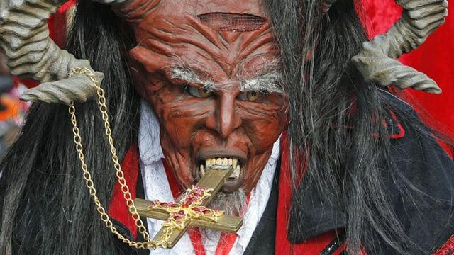 Teufelsmaske mit einem Kreuz im Mund.