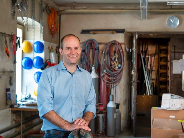 Mann steht in einer Werkstatt.