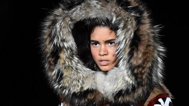 Eine Frau trägt eine Jacke mit einer Pelzkapuze