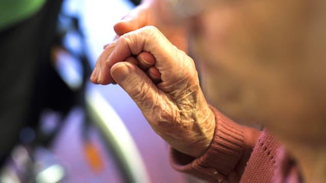 Nahaufnahme der Hand einer Greisin. Die Hand liegt in derjenigen einer Pflegerin.
